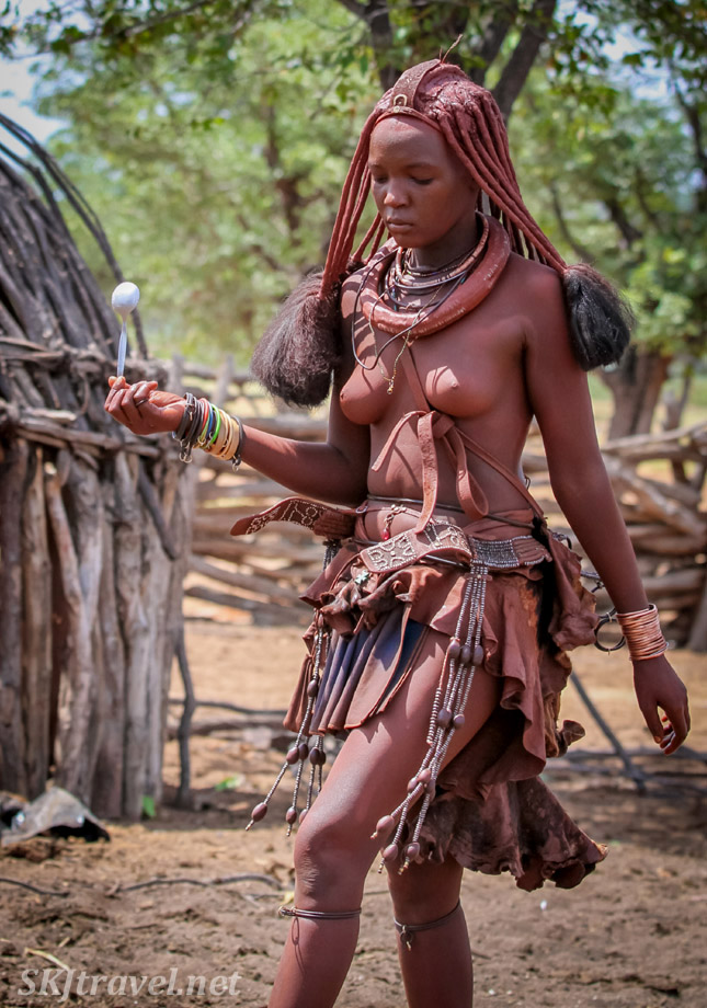 Princess Kaviruru of the Himba tribe of Namibia crossing her kraal carrying a spoon.