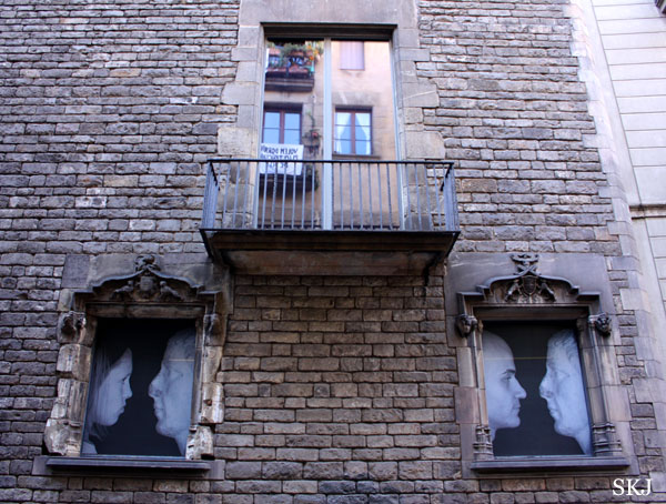 Windows painted black with white faces in Barcelona. Photo by Shara Johnson