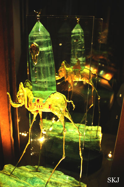 Jewelry creation of golden elephant with spindly legs and large green crystal on top by Dali, called the space elephant. photo by Shara Johnson