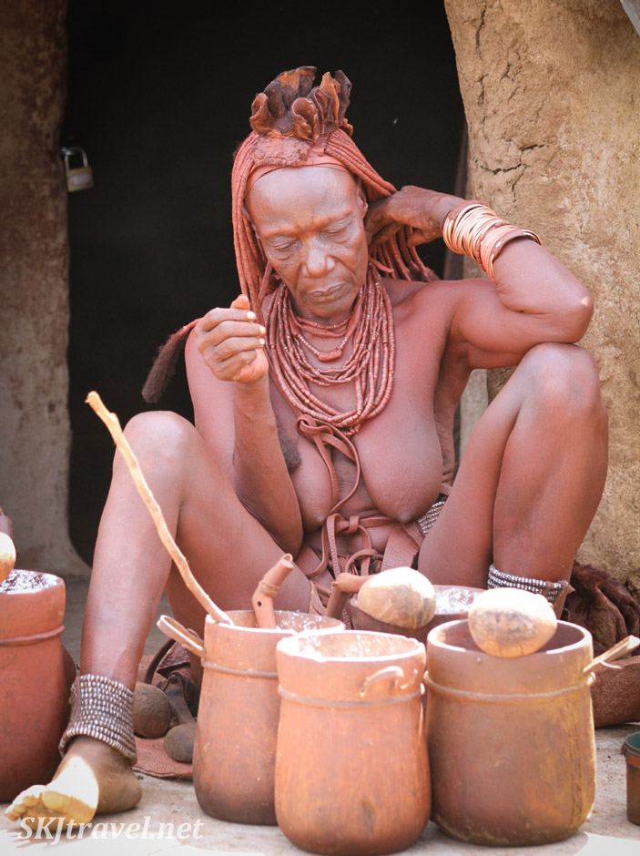 Himba woman with clay pots of mealy outside her hut. Northern Namibia.