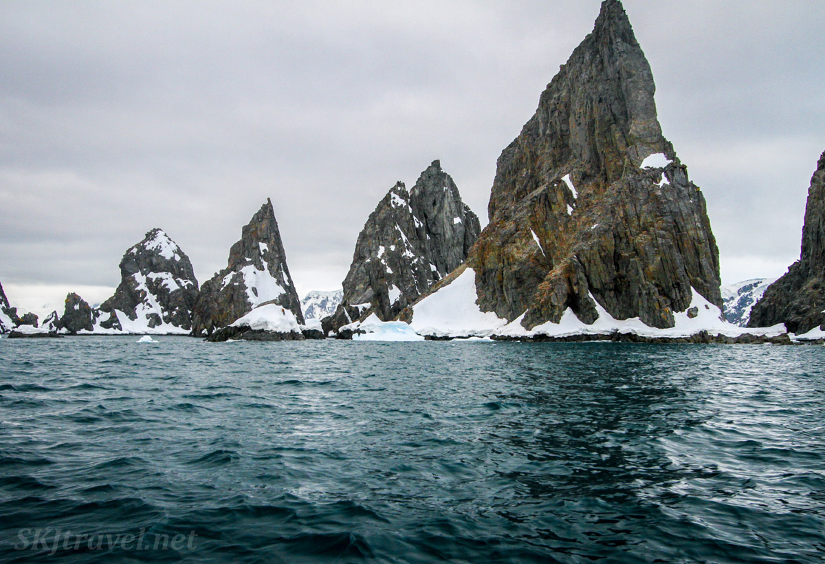 Sharp rock formations jutting out of a green sea. Spert Island, Antarctica.