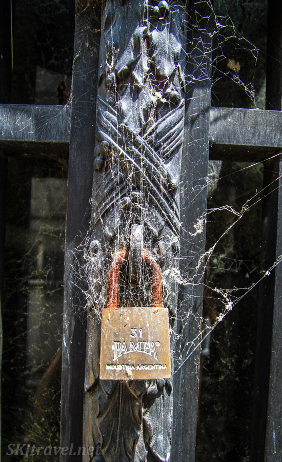 Padlock enshrouded in cobwebs on the doors to a mausoleum in Recoleta Cemetery, Buenos Aires, Argentina.
