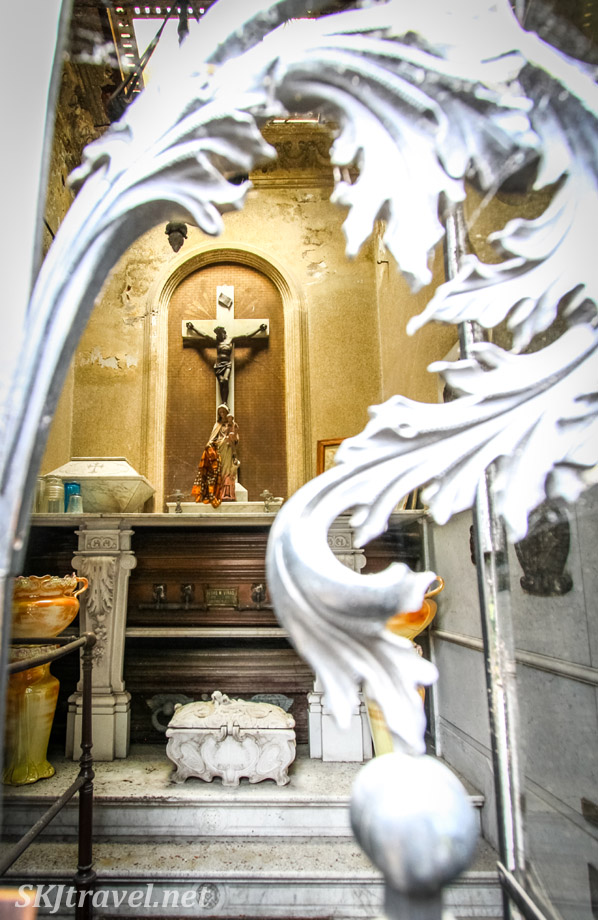 Elaborate interior of mausoleum at Recoleta Cemetery, Buenos Aires, with coffins, cross, offering table and boxes.