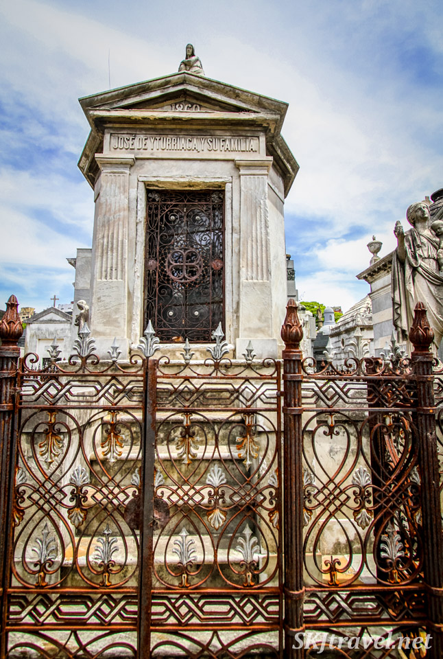 Mausoleum in the style of a small temple with rusting fence in Recoleta Cemetery, Buenos Aires, Argentina.