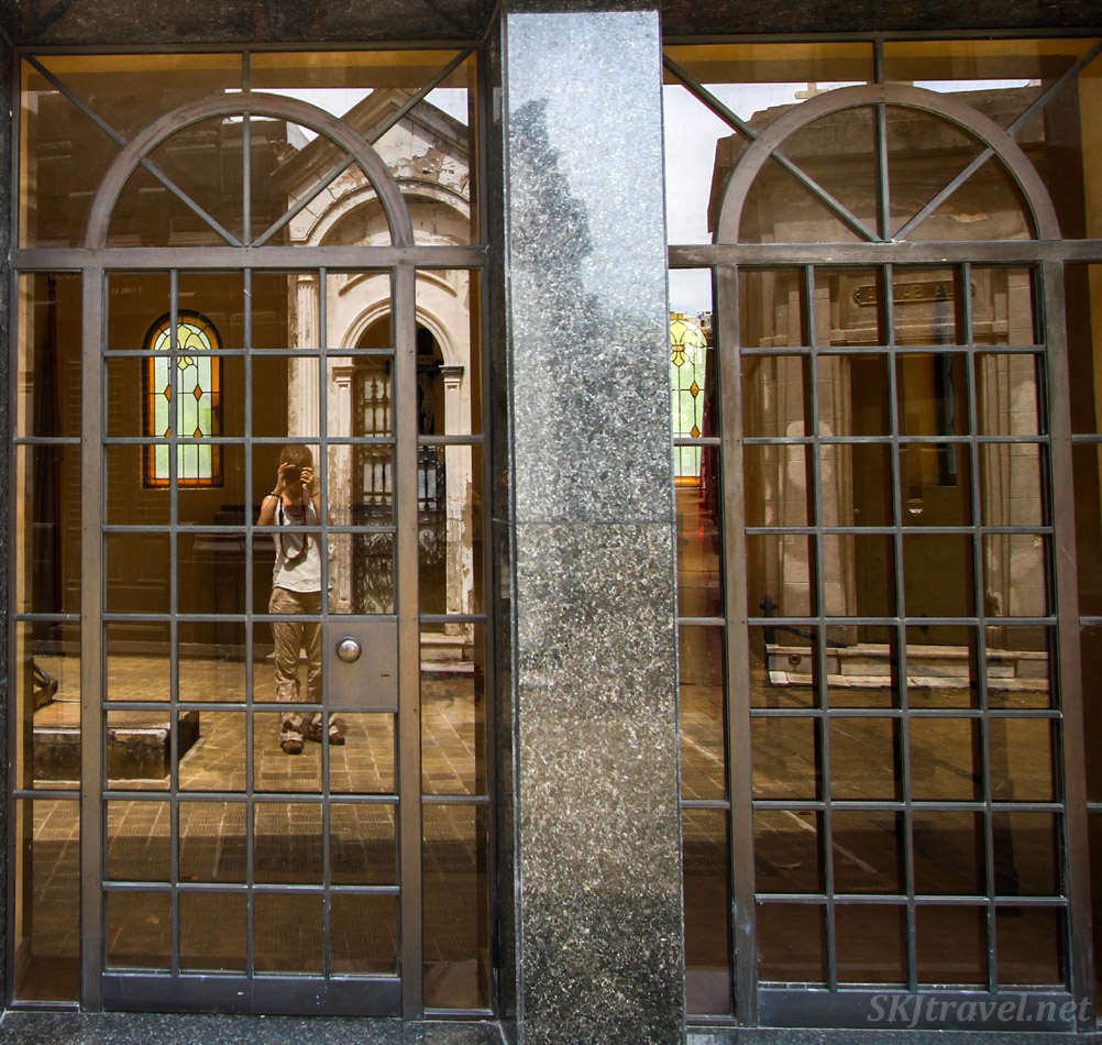 Reflection selfie in the doors of a mausoleum in Recoleta Cemetery, Buenos Aires, Argentina.