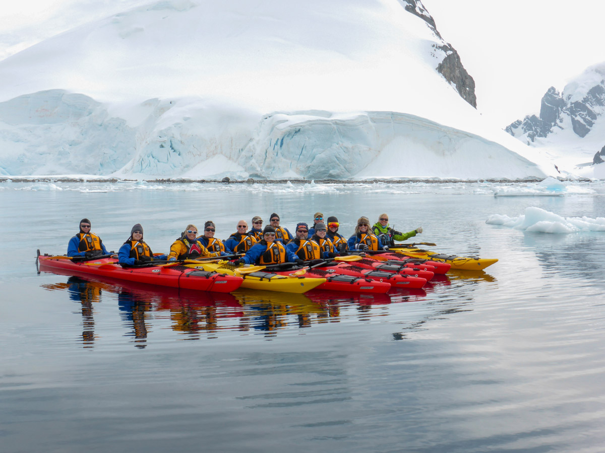 Paddling on calm glassy water at Cuverville Island, Antarctica.