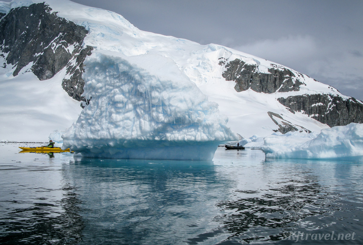 Kayaking among icebergs at Cuverville Island, Antarctica. One kayaking guide on the left, one in the zodiac on the right.