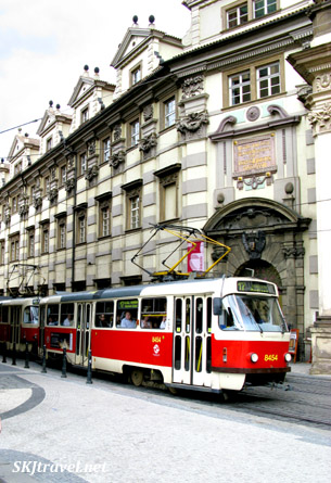 Red tram on narrow cobblestone street with tall buildings in Prague.