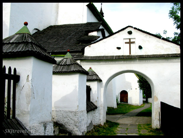 White church buildings and arch with pathway