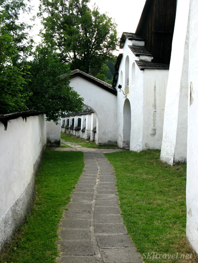 pathway through arch and white building on the side