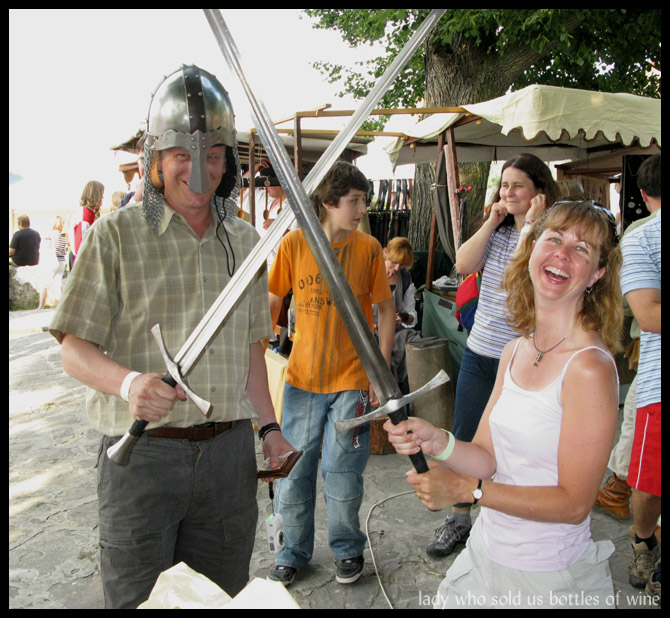 Two people with helmets and swords mock fighting.