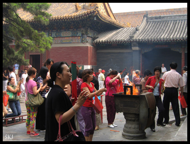 People making offerings and burning incense at the Lama Temple in Beijing, China.