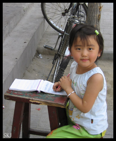 Little girl with her schoolbook and pencil on the sidewalk in Yulin City. Shaanxi Province, China.