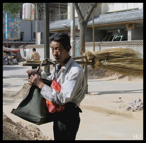 Man carrying brooms made of dried weeds across the street in Yulin City. Shaanxi Province, China.