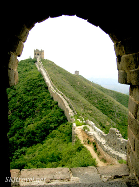 looking through window arch at decaying wall, Great Wall, China.