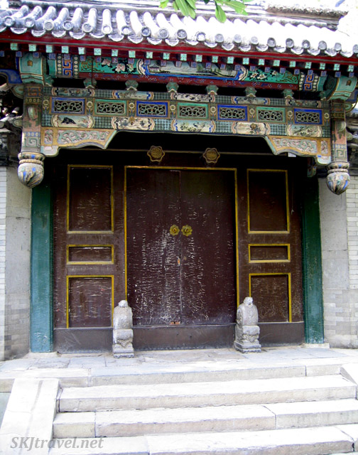 A weathered door still retains the splendor of days past in its roof tiles and painting. Summer Palace, China.
