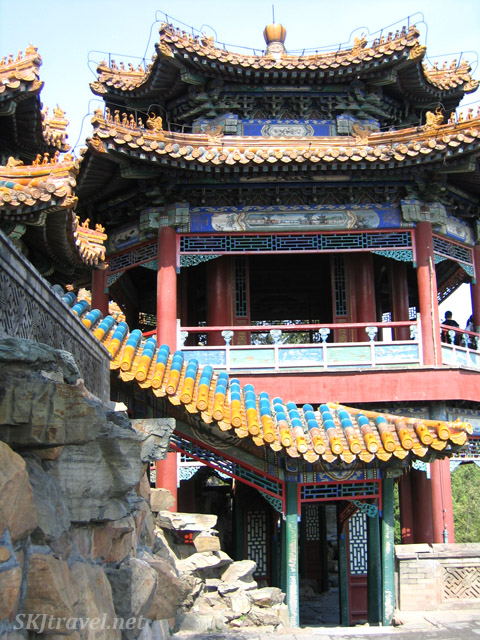 The pagodas and walkways are nestled into the hillside and rocks. Summer Palace, China.