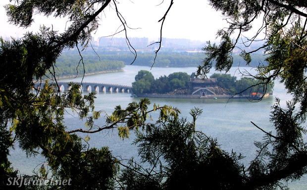 Looking down on Kunming Lake and the 17-Arch Bridge with Beijing cityscape in the background. Summer Palace, China.