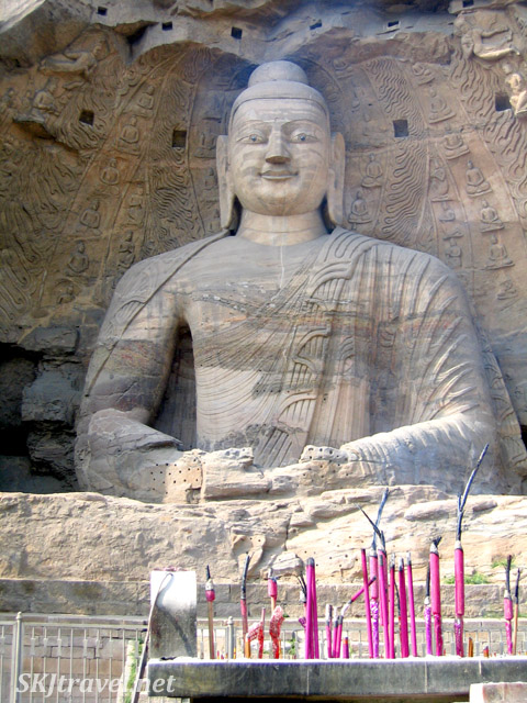 large buddha carved into stone with incense sticks in front