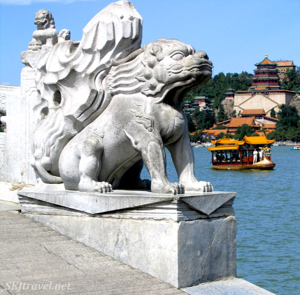 Standing on the 17-Arch Bridge looking across Kunming Lake with a boat on it toward the complex of buildings on Longevity Hill. Summer Palace, China.