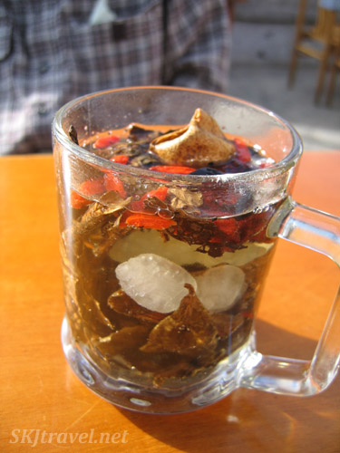 Ostensibly a glass of Tibetan-style tea, complete with all kinds of indentifiable ingredients. Xiahe, China.