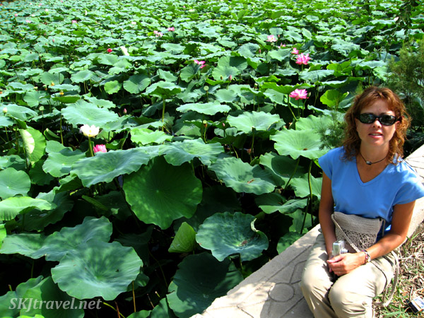 girl sitting next to pond full of water lilies