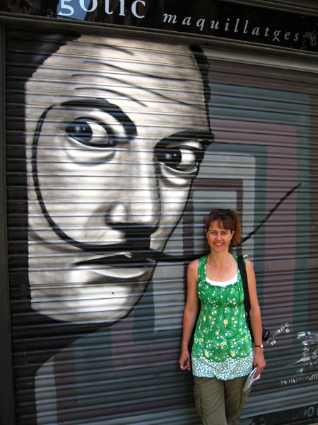 Girl standing with street art mural of Dali in Barcelona.