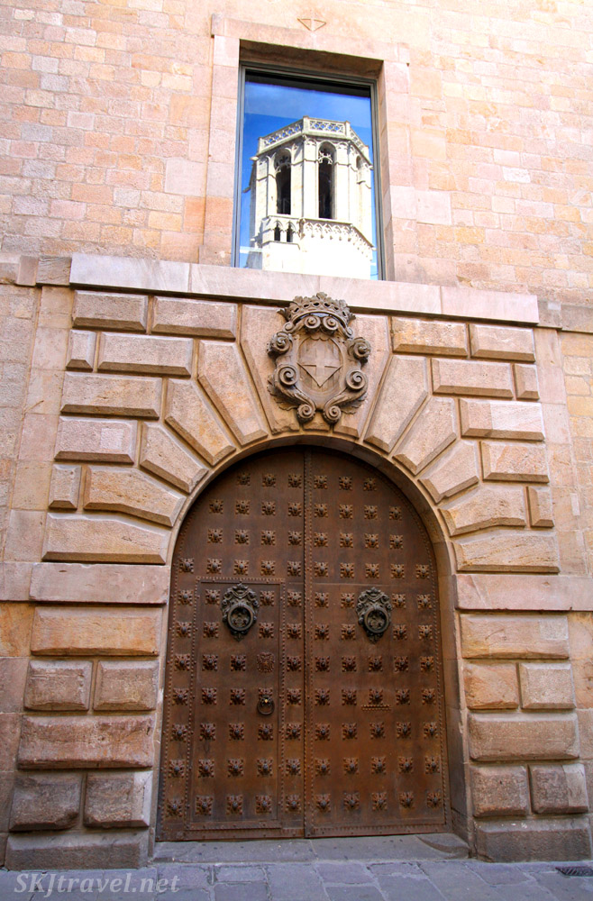 Reflection of a turret in a window above a large arched doorway. Gothic Quarter, Barcelona, Spain.