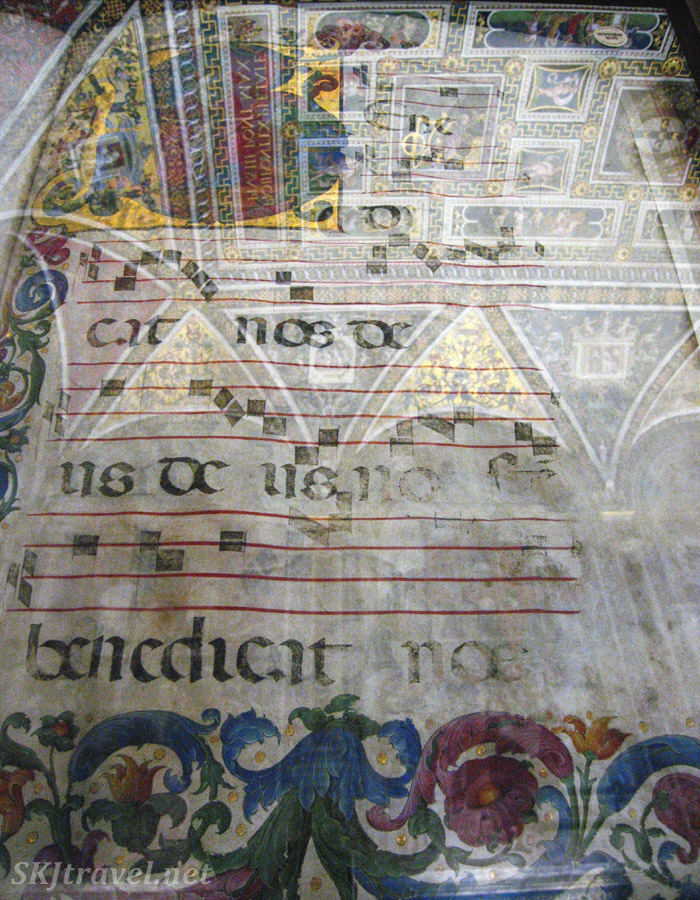 Ceiling of choir chapel reflected in glass case protecting ancient choir score. Cathedral at Siena, Italy.