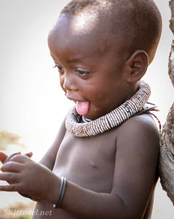 Himba toddler engaged with something her hands with her tongue sticking way out. Kunene region, Namibia.