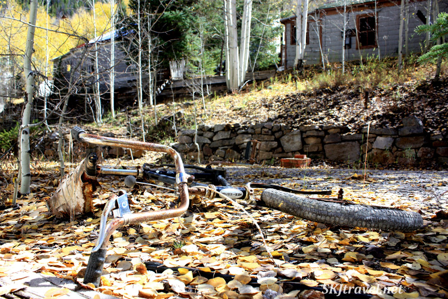 Old bicycle abandoned in the ghost town of Gilman, Colorado. Golden autumn leaves litter the ground.