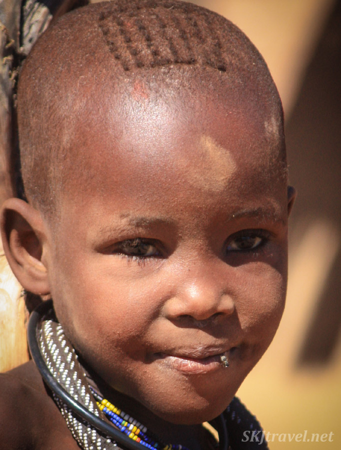 Close-up portrait of Himba child, Namibia. A fly on her lip.