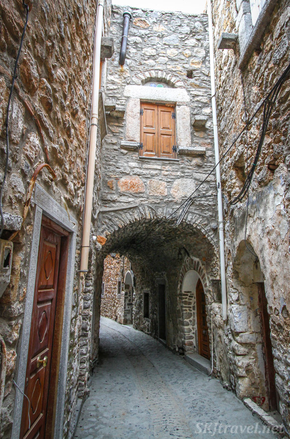 Alleyway with stone bridge over it, medieval city center of Mesta, Chios Island, Greece.