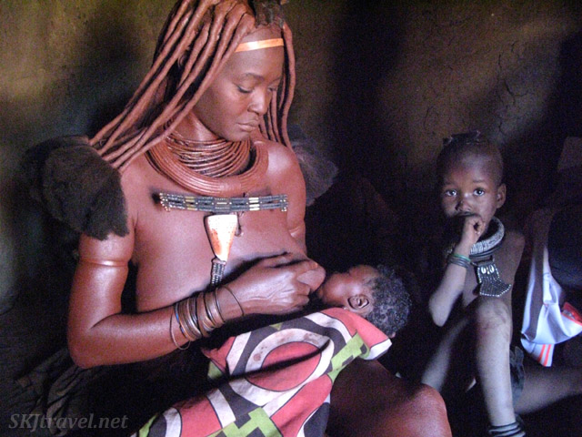 Mother from Himba tribe nursing a newborn inside her hut. Namibia.