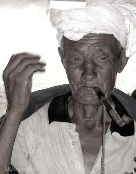 Old Chinese man smiling with a pipe in his mouth.