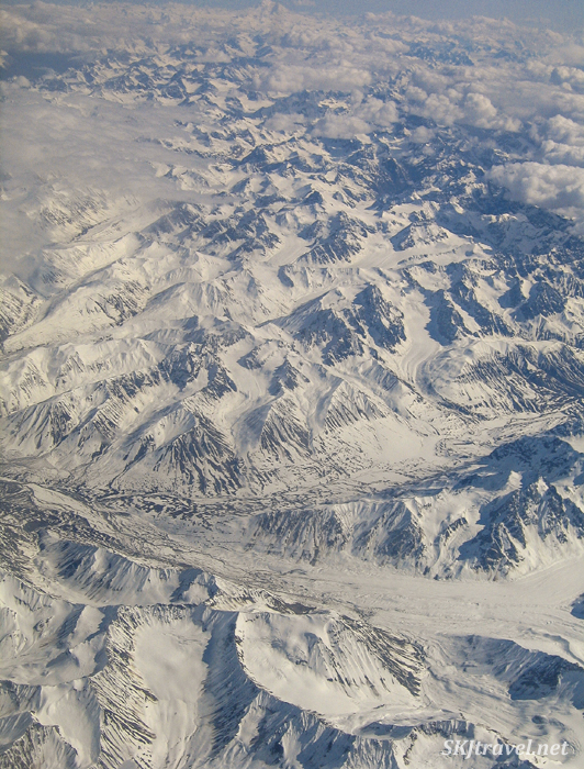 View of Alaskan mountain range from an airplane window.