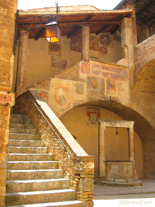 Stone stairs around a well with coats of arms painted on the stairway corridor. photo by Shara Johnson