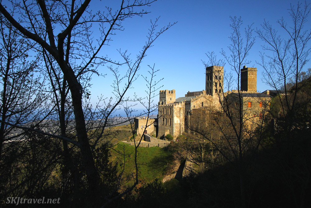 View of Sant Pere de Rodes monaster through the trees. Near Port de la Selva, Spain.