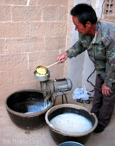 Chinese man ladels crushed soybeans with water into an electric grinder, a village in Shaanxi Province, China. Photo by Shara Johnson