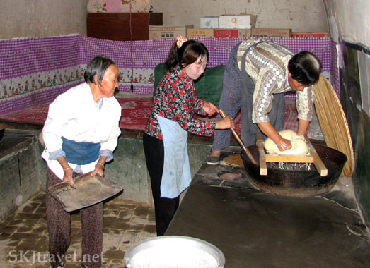 Three women work in the kitchen, one presseing liquid through a cheese cloth into a giant skillet stirred by another, in a village in Shaanxi Province, China. Photo by Shara Johnson