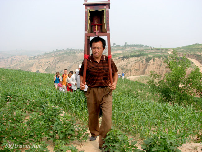 Carrying a portable temple on his shoulders through the crop fields from a village temple near Dang Jiashan, China.