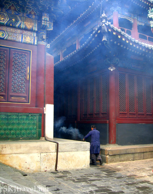 A monk pushes a wheelbarrow of smoldering incense through a narrow corridor between two ornately decorated temples at the Lama Temple in Beijing, China. Photo by Shara Johnson