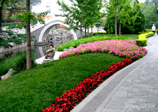 Bright flowers along a canal in a pretty park near Tiananmen Square. Beijing.