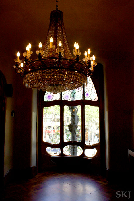 Main floor of the Batllo looking out onto the street through colored glass with large chandelier, Barcelona. photo by Shara Johnson