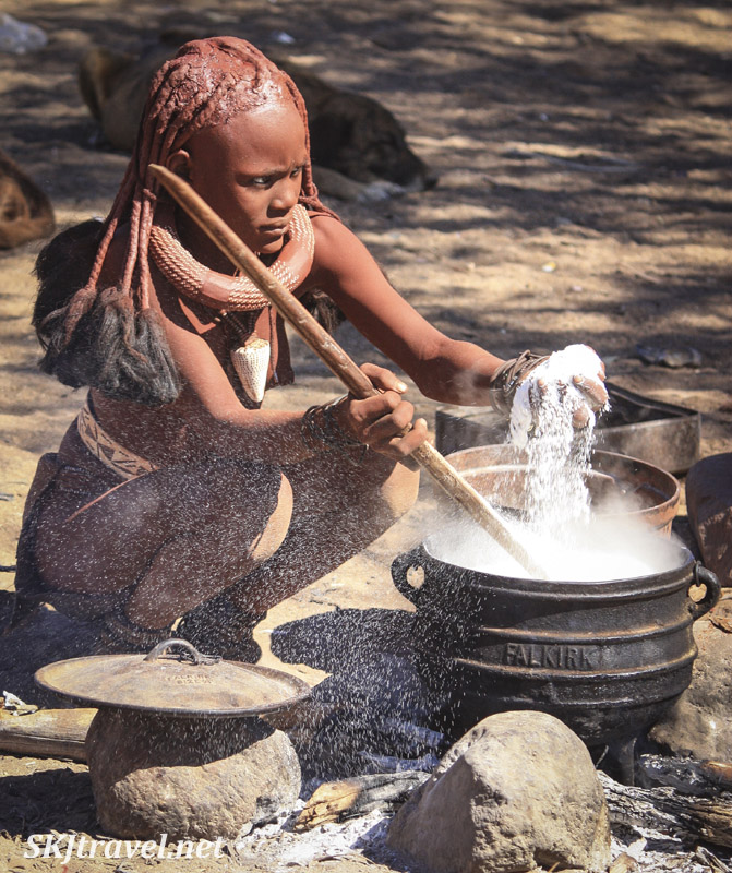Young Himba woman making porridge over a live fire, Kaokoland, Namibia.