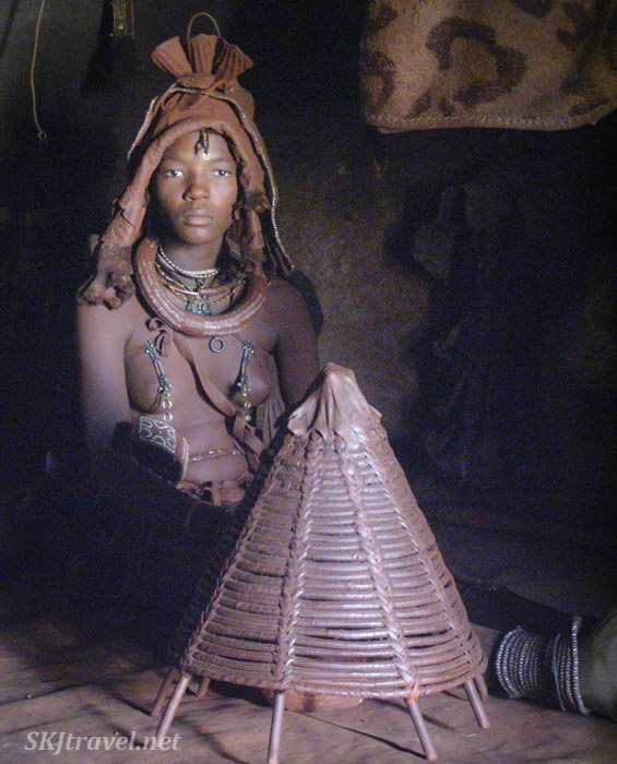 Young Himba princess sitting inside her hut in her traditional kraal, Kaokoland, Namibia.