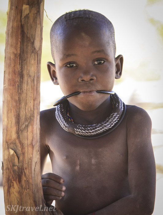 Himba child sucking on her necklace. Kaokoland, Namibia.