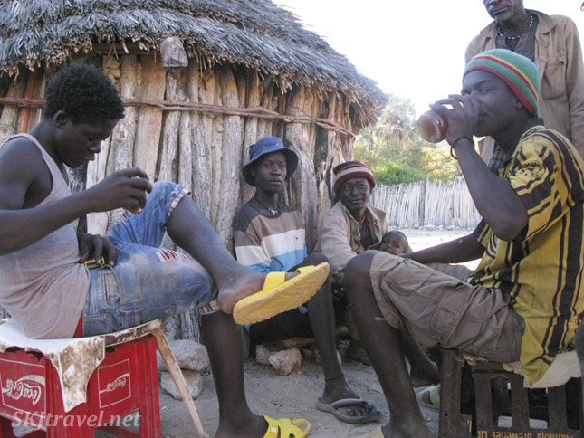 Men drinking homemade alcohol outside a hut in a non-traditional village near Epupa Falls, Kaokoland, Namibia.