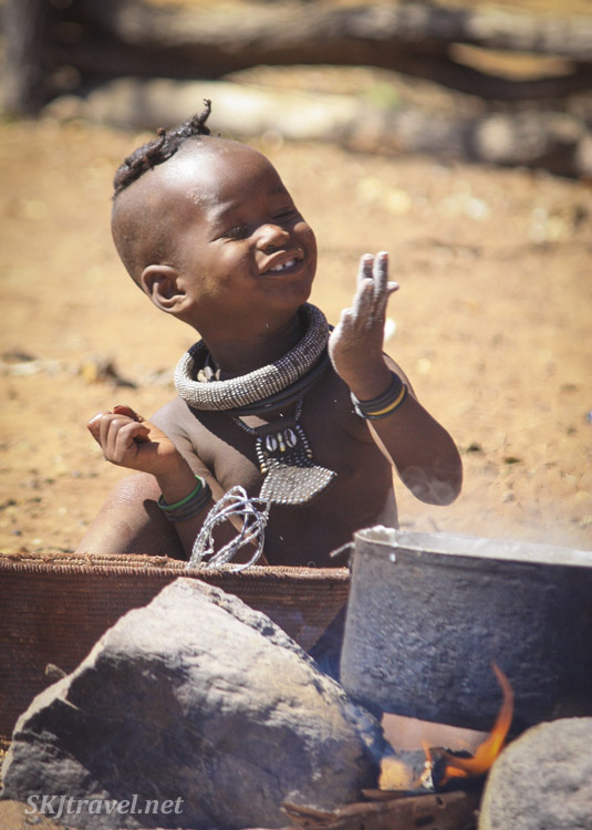 Himba toddler playing in a basket of flour. Kaokoland, Namibia.