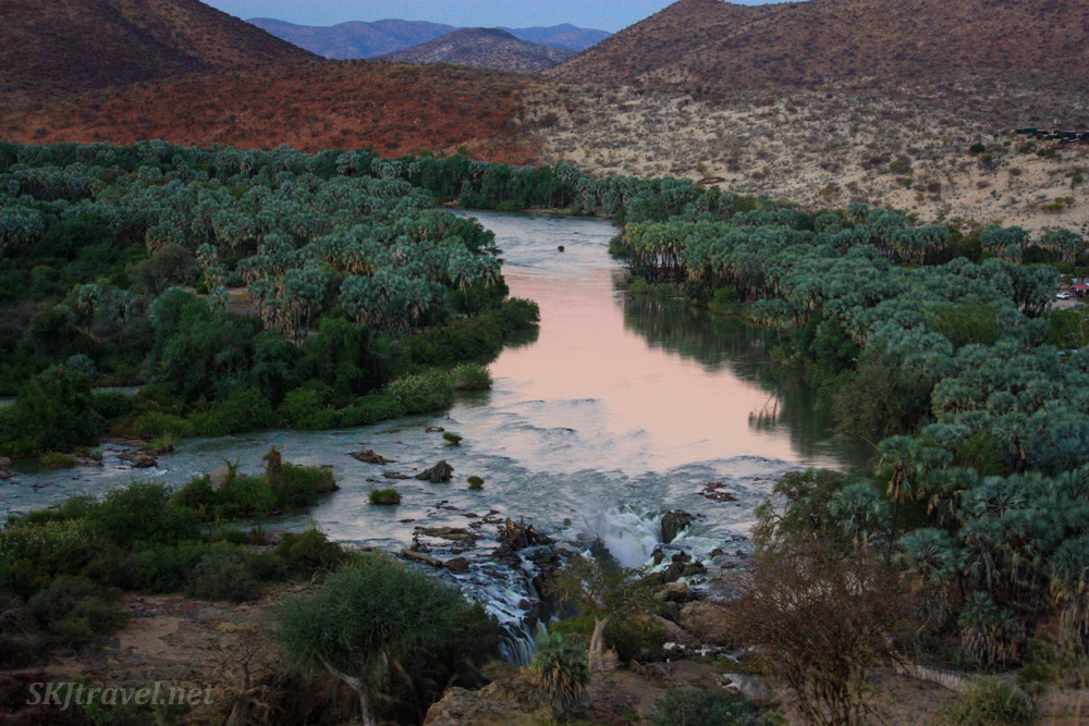 The Kunene (Cunene) River snakes across a valley in Kaokoland, Namibia, flanked by dense trees.